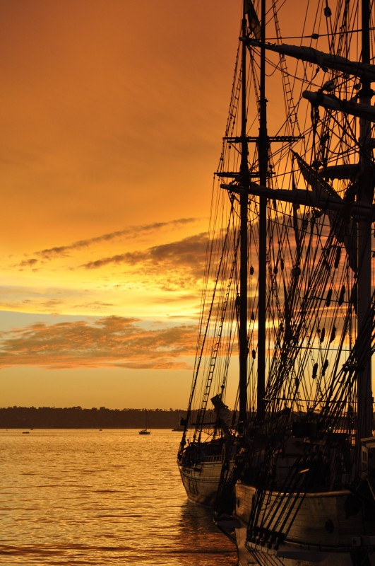 The sun setting in the rigging of nearby tall ships (not the Adventurer).
